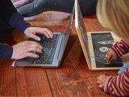 Padre usando el ordenador portátil sentado en el suelo con la hija dibujando en el ordenador portátil de juguete - foto de stock