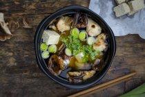 Tazón de fuente de sopa de miso con tofu orgánico, hongos shitake, puerro y perejil en madera oscura - foto de stock