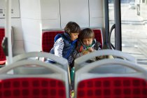 Two little boys sitting in bus playing with smartphone — Stock Photo