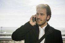 Молодой бизнесмен в аэропорту с помощью смартфона — стоковое фото