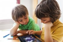 Two little brothers playing with digital tablet — Stock Photo