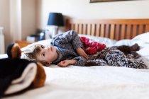 Маленький хлопчик, лежачи на ліжку і, дивлячись на камеру — стокове фото