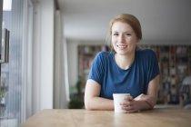 Femme assise à table avec une tasse de café — Photo de stock