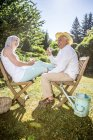 Happy elderly couple sitting on wooden chairs in garden with cups of coffee — Stock Photo