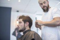 Giovane uomo ottenere acconciatura al negozio di barbiere — Foto stock