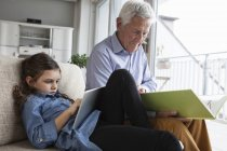 Grandfather and his granddaughter sitting together on the couch with book and digital tablet — Stock Photo