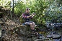 Турист в лесу сидит на скалах у ручья и делает селфи — стоковое фото