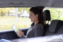 Smiling businesswoman using digital tablet in car — Stock Photo