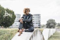 Jeune homme d'affaires, assis sur le mur dans le parc de la ville — Photo de stock