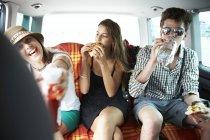 Трое подростков друзей, закусывали в автомобиле — стоковое фото