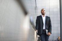 Uomo d'affari con la compressa cammina davanti all'edificio — Foto stock