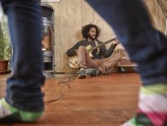 Junger Mann spielt E-Gitarre am Kamin mit Person im Vordergrund — Stockfoto