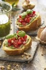 Bruschetta with basil pesto, tomatoes, pine nuts and basil leaves — Stock Photo