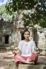 Cambodia, Angkor, Siem Reap, young woman practicing yoga in front of Ta Som temple — Stock Photo