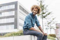 Jovem sentado na parede e sorrindo na rua — Fotografia de Stock
