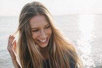 Портрет счастливой молодой женщины перед морем — стоковое фото