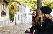 Due giovani donne che si siede su una panchina nelle strade di Montmartre — Foto stock