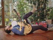 Uomo che suona la chitarra elettrica davanti all'albero di Natale — Foto stock
