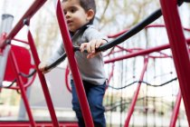 Toddler playing on red playground equipment outdors — Stock Photo
