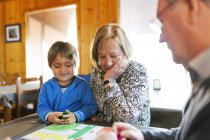 Grandparents playing ludo with grandson — Stock Photo