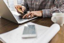 Обітнутого зображення людини, використовуючи ноутбук і Холдинг кредитної картки — стокове фото