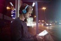 Человек с наушниками, сидящий на автобусной остановке с помощью цифрового планшета ночью — стоковое фото