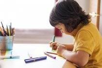 Side view of little boy drawing at home — Stock Photo
