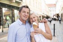 Portrait of happy senior couple with ice cream cone — Stock Photo