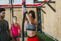 Athleten, die beobachtete Frau ein Kletterseil in Turnhalle — Stockfoto
