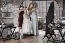 Mother and bridesmaid helping bride putting on wedding dress — Stock Photo