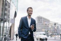 Германия, Берлин, улыбающийся бизнесмен с мобильным телефоном — стоковое фото
