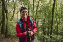 Hiker man with walking sticks laughing in forest — Stock Photo