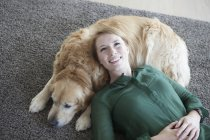 Femme détente avec chien sur tapis — Photo de stock