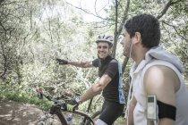 Человек на горном велосипеде в лесу разговаривает с молодым человеком — стоковое фото