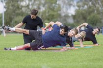 Coach doing exercises with team on sports field — Stock Photo
