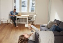 Couple relaxing with book and laptop at home — Stock Photo