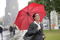 Mulher de negócios feliz Alemanha, Berlim, com o guarda-chuva vermelho na Potsdamer Platz — Fotografia de Stock