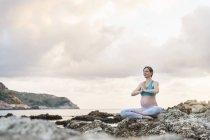 Femme enceinte, pratiquer l'yoga en mer — Photo de stock