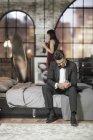Homme élégant sur le lit s'habiller avec femme sur fond — Photo de stock