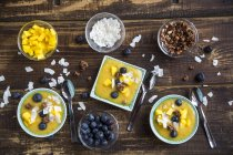 Bowls of mango smoothie with diced mango, coconut flakes, blueberries and choco crunch — Stock Photo