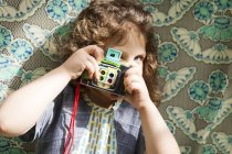Little girl taking a picture with vintage camera — Stock Photo