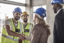 Construction worker and executive shaking hands in construction site — Stock Photo