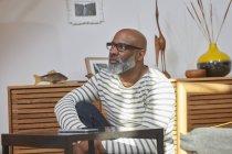 Застенчивый человек, сидящий в гостиной — стоковое фото