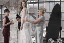 Mutter und Brautjungfer braut brautkleid anziehen helfen — Stockfoto