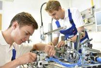 Zwei Studenten arbeiten mit pneumatischen Bauteilen — Stockfoto