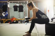 Female boxer taking a rest in the gym — Stock Photo