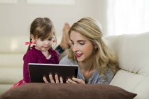 Mother and little daughter lying together on couch in living room and using digital tablet — Stock Photo
