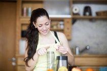 Lächelnde Frau bereitet Essen in ihrer Küche zu — Stockfoto