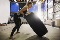 Woman exercising with tire in gym — Stock Photo
