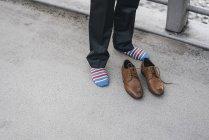Молодий чоловік у шкарпетки, стоячи з шкіряного взуття попереду на вулиці — стокове фото